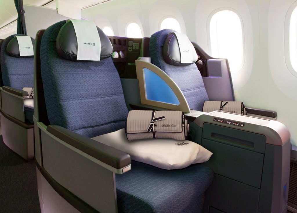 Two legacy business class seats on United. They do not offer direct aisle access. They can be seen with soft product, including a blanket and pillow, on the seat bottom