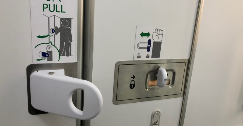 Jamco aircraft lavatory door handle with instructions on how to use wrist and be hands free opening and closing it. Part of touchless travel.