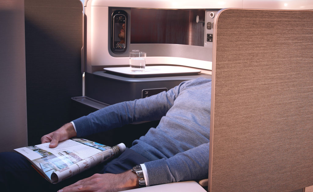 A man reclines in the new Recaro business class seat. He is seen from the side. The door of the suite is open. He has a magazine on his lap and a watch on his wrist.