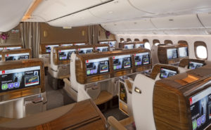 Rows of business class seats on board an Emirates widebody. Emirates' signature burled walnut furniture is in clear view, with large seatback IFE screens