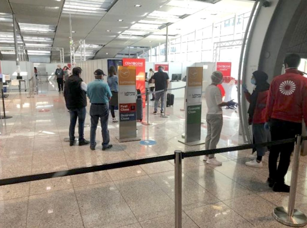 Passengers, wearing masks, wait to be tested at the airport