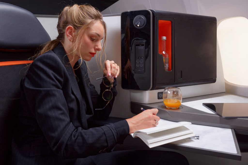 Opera's tray table is shown. It slides out. A woman, seated in Opera, is writing in a notepad on the table.