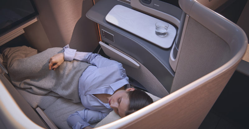 Recaro's CL6720 business class suite is shown. It offers great privacy. A man is seen sleeping in privacy