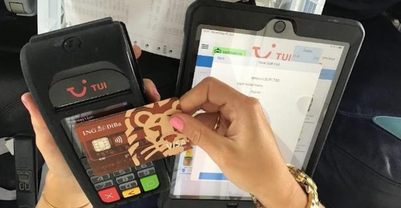 A woman makes a credit card payment via a point of sale device aboard TUI Airlines