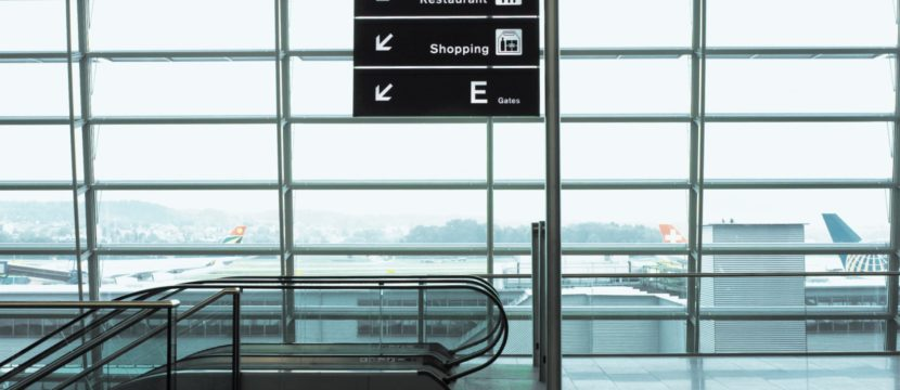 An airport sign showing directions to the dining and gates. An escalator is shown, and windows in the background