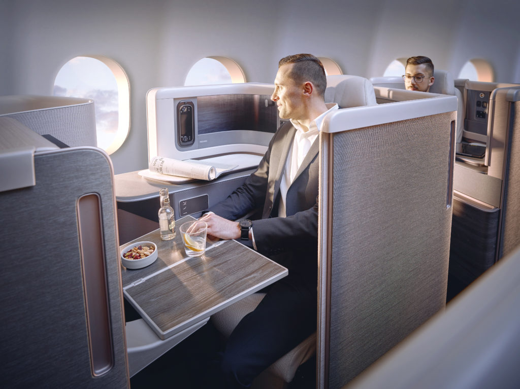 A man looks out the window of an aircraft, whilst seated in the new Recaro business class seat. He has nuts and a drink in front of him.