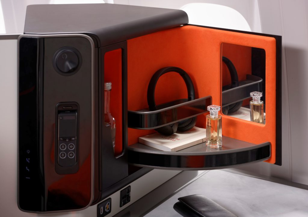 A close-up view of the side storage area of Opera. A headset and a bottle of perfume are displayed in a pull-out compartment. The interior of the compartment is bright orange, and includes a small mirror.