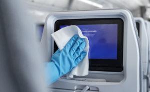 A gloved hand wipes down a seatback IFE screen
