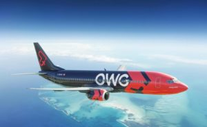 An OWG 737 flying, with a blue sky. The aircraft livery is red and blue, with OWG in white lettering on the side