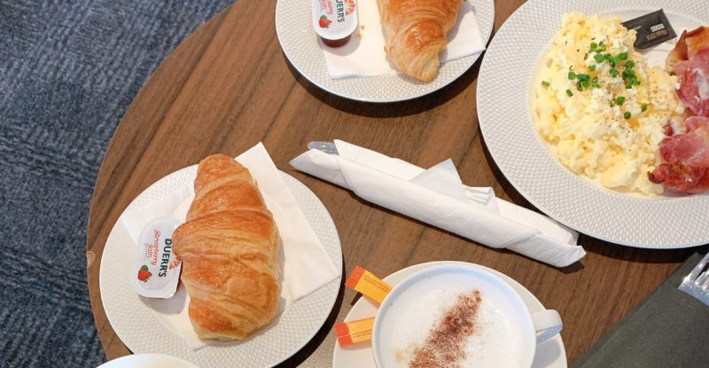 A table with various plated dishes, including a full breakfast with eggs and bacon, and croissants