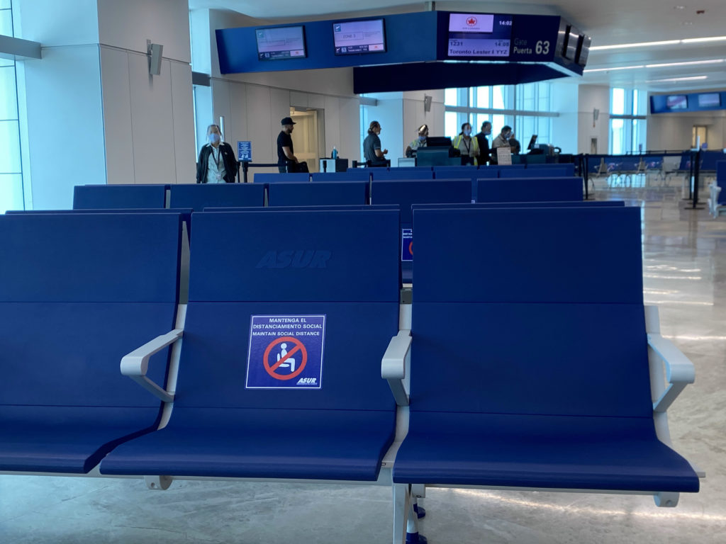 Blue seats at the gate at CUN with screens overhead. A social distancing decal is seen on a seat.
