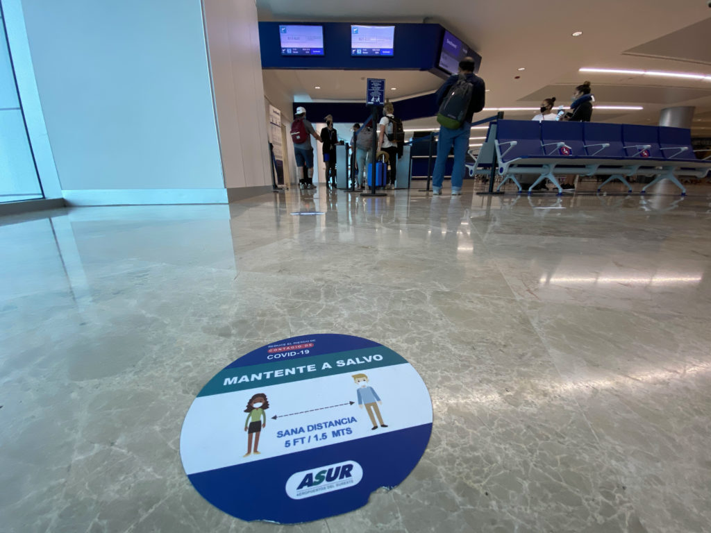 A social distancing marker on the ground at CUN, with screens overhead. Two queues are formed on either side of the agent's desk for boarding