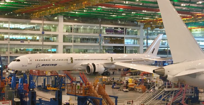 A 787-10 being assembled at Boeing's North Charleston facility in South Carolina. The aircraft is white, and multi-colored ceiling lights can be seen overhead