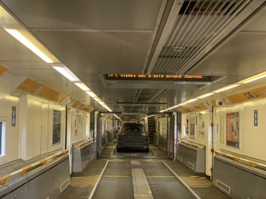 Cars lined up in an enclosed train car with digital signage overhead and yellow lights