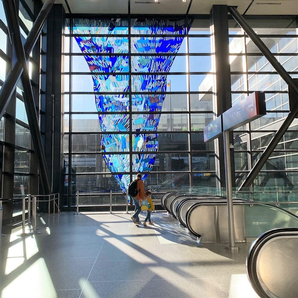 A man and his chid walking towards the escalators at SEA, with a giant blue window art treatment seen in the background