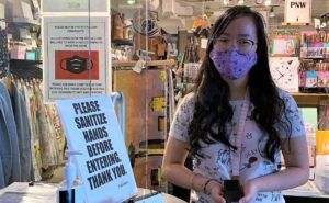 A staffer, in mask, at the Fireworks Gallery. A bottle of hand sanitizer is also seen alongside her.