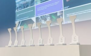 A photo of the long, white Crystal Cabin Award statues lined up in a row on stage in Hamburg