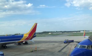 Southwest aircraft at the gate. Global Eagle's Ku-band antenna hump is seen atop the fuselage. This transmits live television and internet to passengers. The aircraft, a 737, is seen in Southwest's colorful livery of blue, yellow and red, with a blue sky and clouds in the background