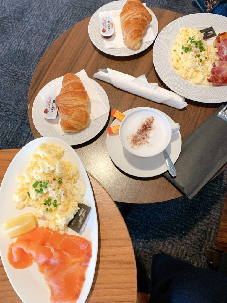 Various breakfast meals sit prominently on two side-by-side tables, including a salmon and eggs breakfast, and separately an eggs and bacon breakfast. Two croissants are also shown, as well as a cup of cappuccino.