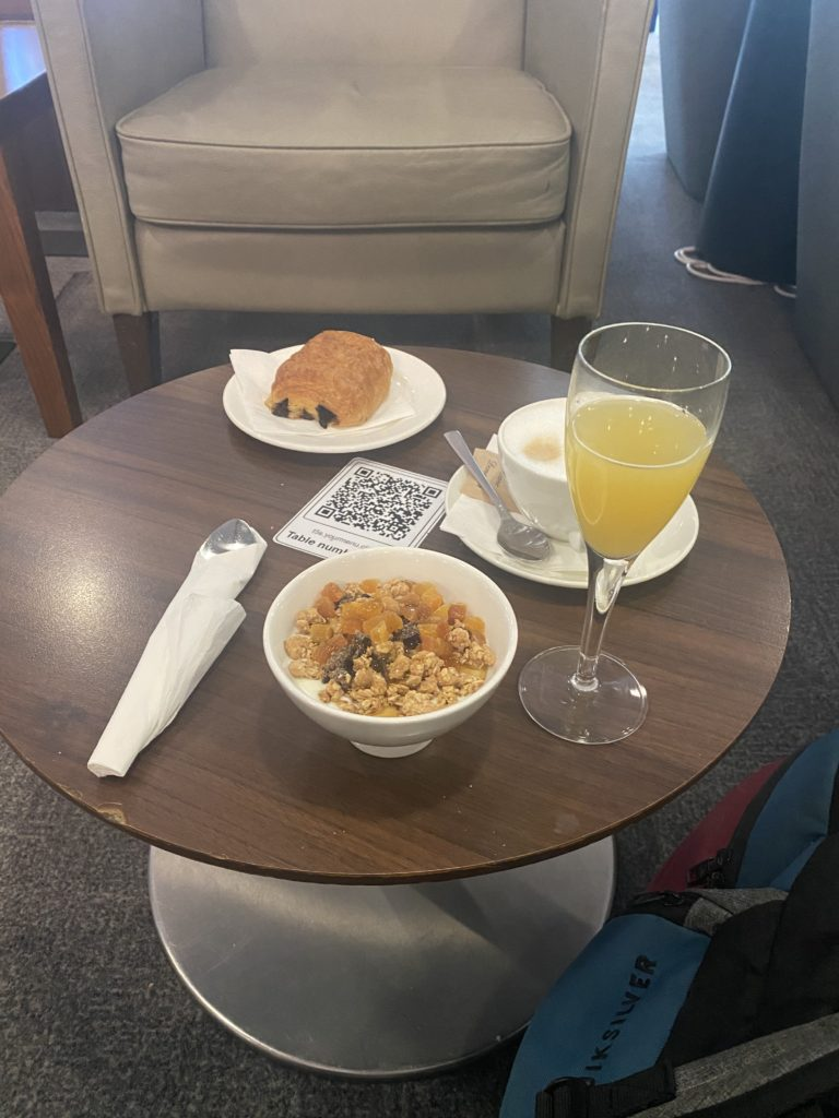 A comfortable beige chair, with a round table in front of it. There is a bowl of cereal, a chocolate croissant and a glass of mimosa on the table.