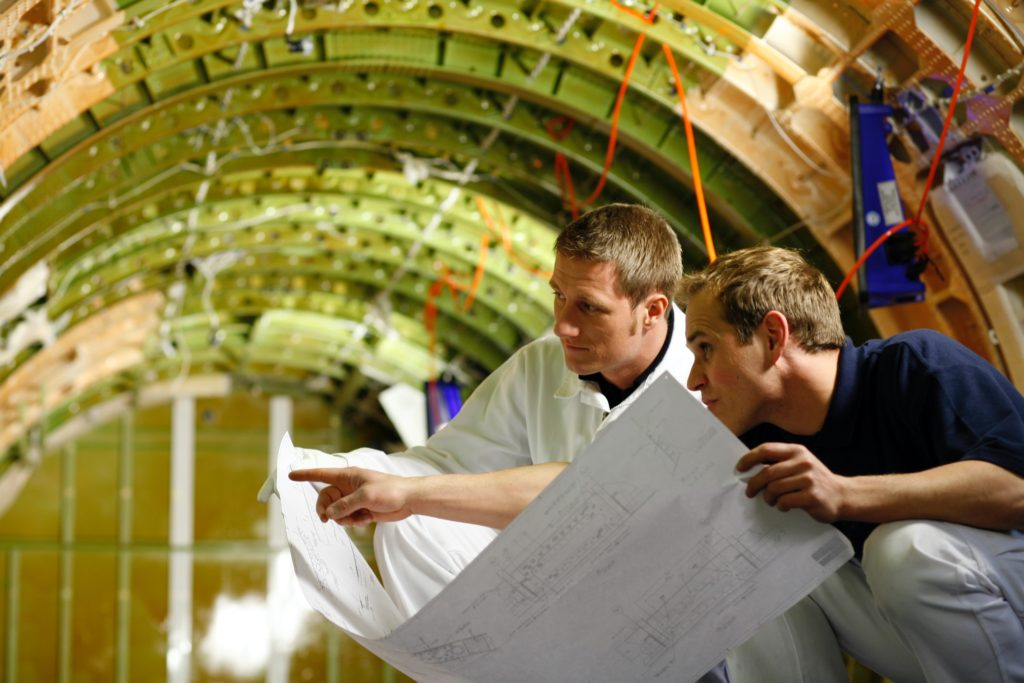 """Inside a """"green"""" aircraft, with no aircraft interiors installed. Two men are seen studying a diagram inside the tube"""