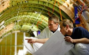 Two men crouched on the floor of a green aircraft, looking at specs for an interior mod