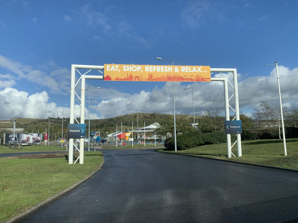 """A large sign in front of the terminal saying: """"Eat, Shop, Refresh & Relax"""". A blue sky and green hills are shown in the background"""