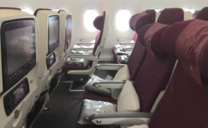 Inside an A350 cabin, with rows of seats and seatback IFE screens