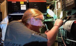 A woman conducts an inspection of an aircraft avionics bay
