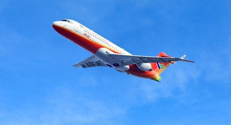 An ARJ21 in white and orange livery in-flight, with a blue sky in the background