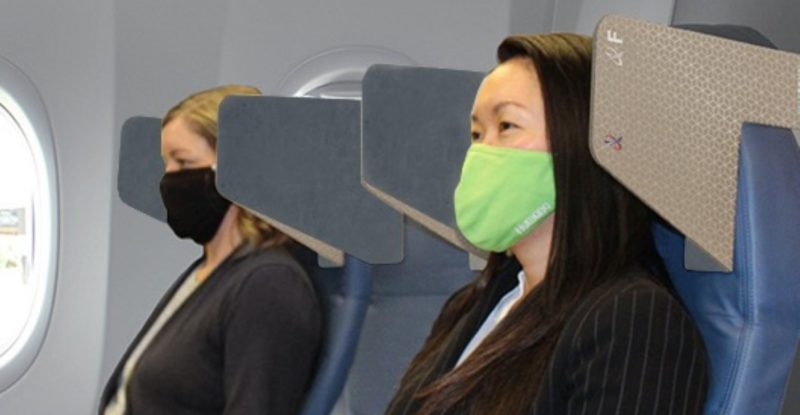 Two passengers, one seated at the window and the other in an aisle seat, are facing forward, with the HeadZone cardboard solution shown in view. Both passengers are wearing masks. HeadZone provides an added layer of privacy to the passengers.