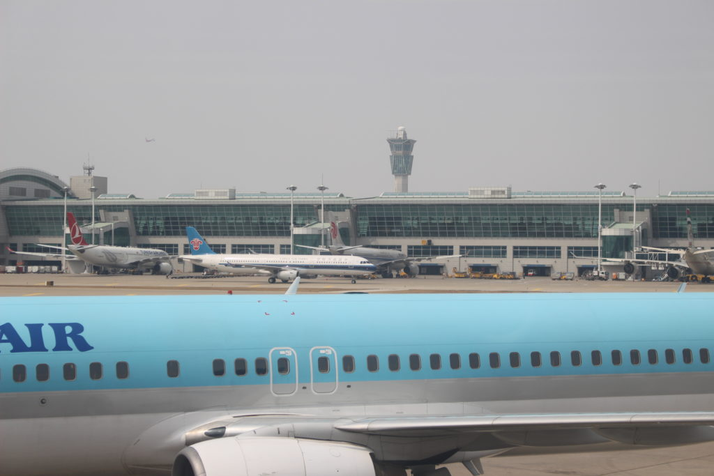 A Korean Air jet parked at the airport. The aircraft is in Korean Air's signature teal, with bold blue lettering being part of the livery