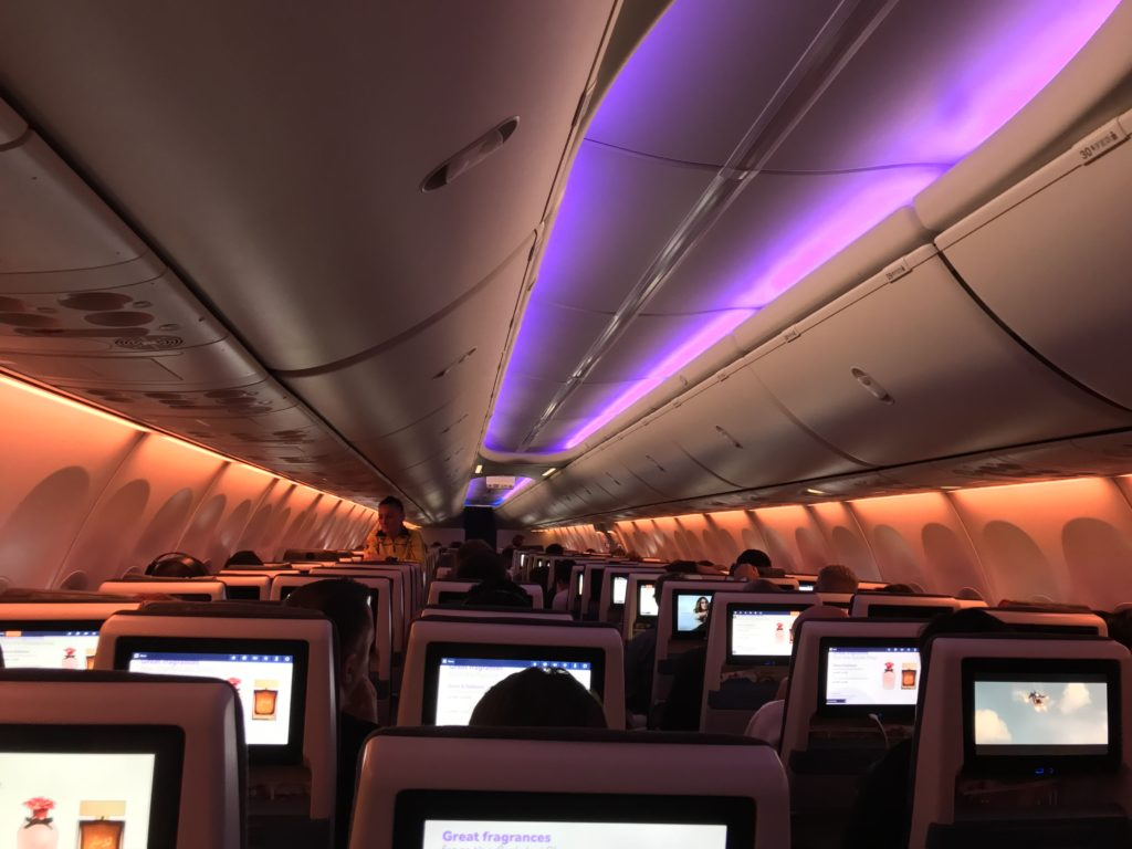 Inside a flydubai MAX with seatback IFE, orange mood lighting on the sidewalls and purple mood lighting on the ceiling