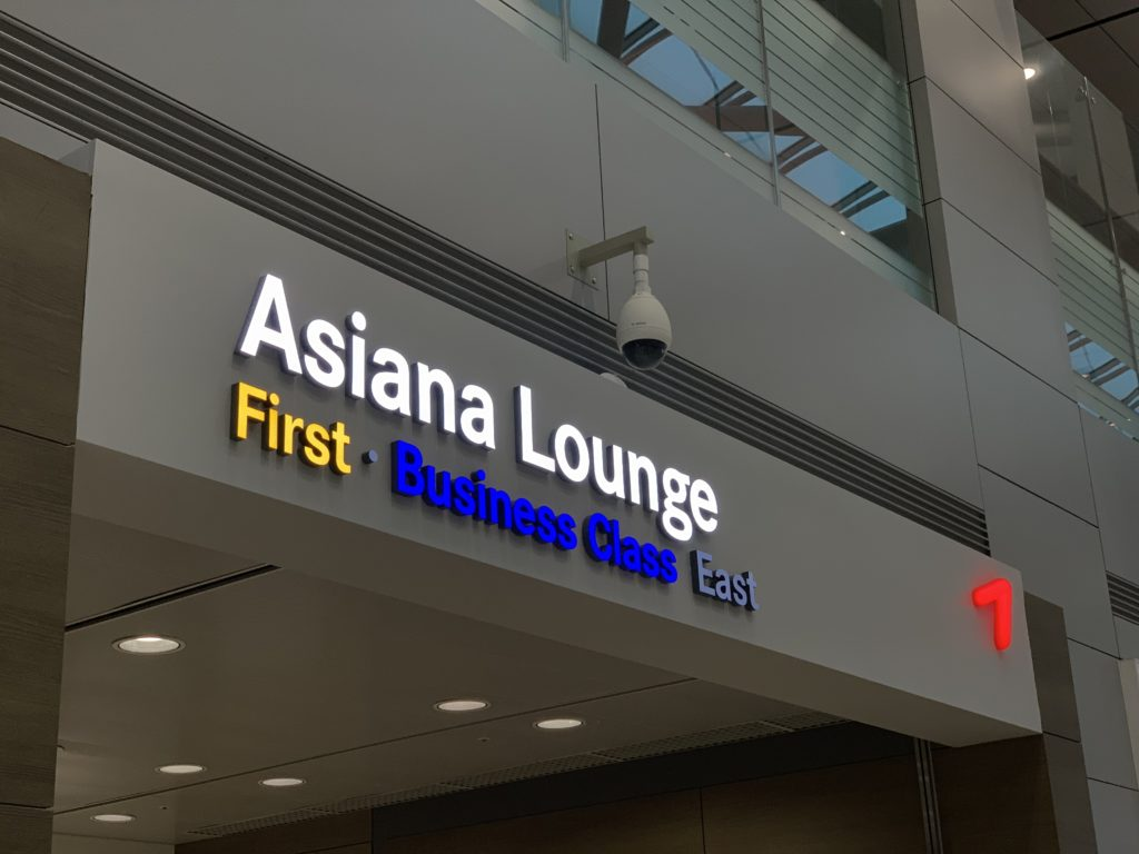 """The sign in front of Asiana's first and business class lounge. Asiana's lettering is white, while the word """"first"""" is yellow and """"business class"""" is in blue"""