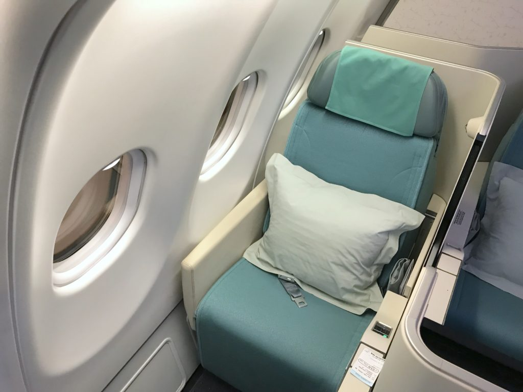 Korean Air's Apex business class seat, with the signature teal seat cover and headrest. A pillow is seen on the seat