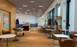 Lufthansa lounge at Brandenburg Airport showing some table seating options and large windows.