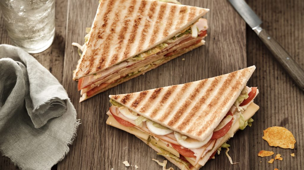 A club sandwich on a wooden table with a glass of water and a knife