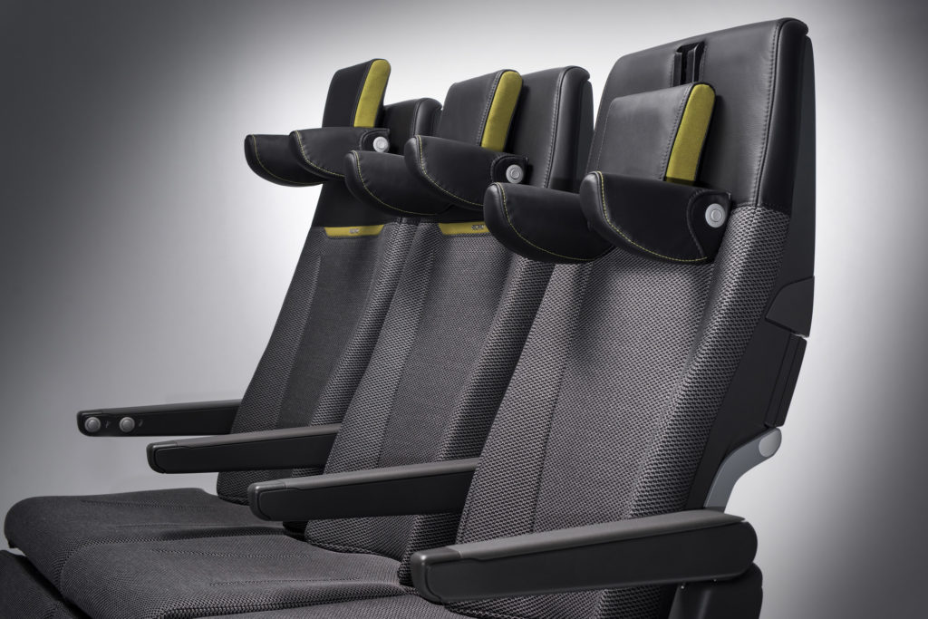 A photo of a seat triple, the Recaro CL3710 seats, in grey with green/yellow accent on the headrest