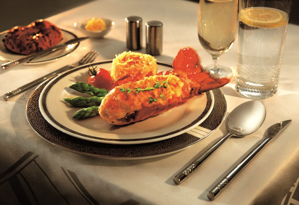 A meal served on board on fine china. A lobster tail is accompanied by two sides. A glass of wine and a glass of water are part of the scene, as are silver salt and pepper shakers