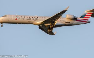 An American Eagle Airlines CRJ700 in-flight, with American's signature flag livery seen in the shot. A blue sky in the background.