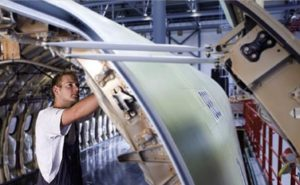 man working on aircraft frame in a hanger