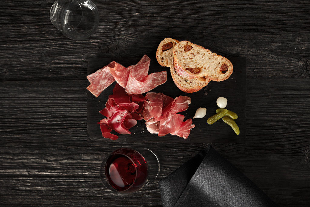 A selection of meats with slices of bread and gherkins