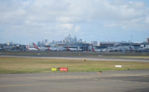 An image of Sydney Airport from the runway. A blue sky serves as a backdrop to the terminal