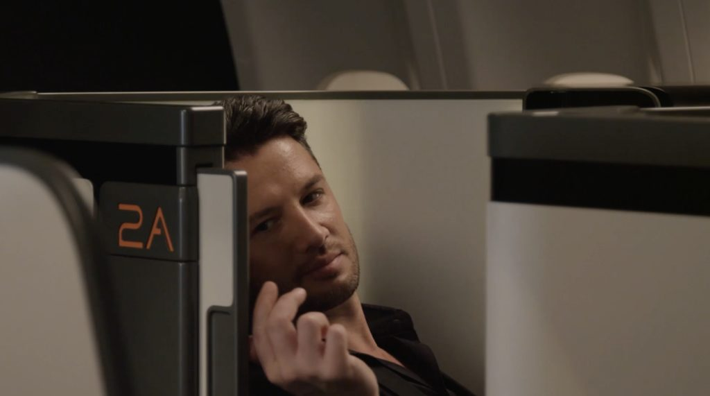 A white male leans his head against the shell of a business class suite. His hand is sliding the door open
