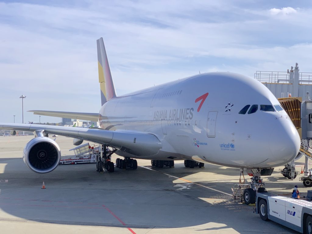An Asiana A380 parked at the gate, with a blue sky in the background
