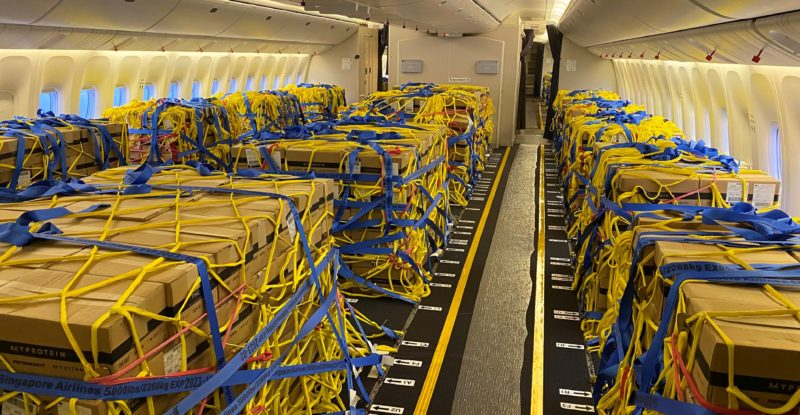 Cargo loaded into a 777 aircraft cabin, with nets and tie-downs