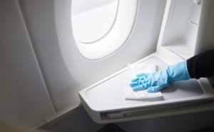 A gloved hand wipes down the hard surfaces of a business class seat aboard an aircraft