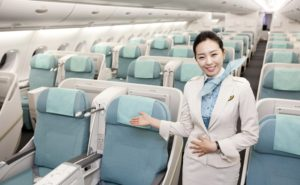 A Korean Air widebody with signature teal seats, and a smartly-dressed flight attendant