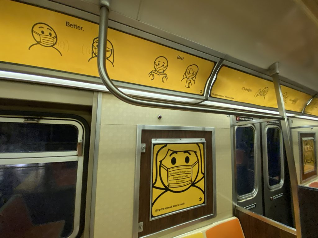 Inside a subway car. Yellow signage shows passengers how to correctly wear a mask.