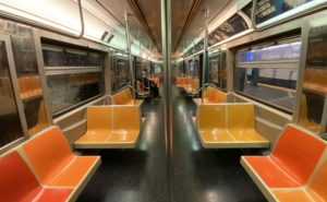 A near-empty subway car, with orange and yellow seats. The car appears to be sparkling clean